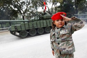 A girls poses next to a tank after the military parade to commemorate the 20th anniversary Venezuelan President Hugo Chavez's failed coup attempt in Caracas
