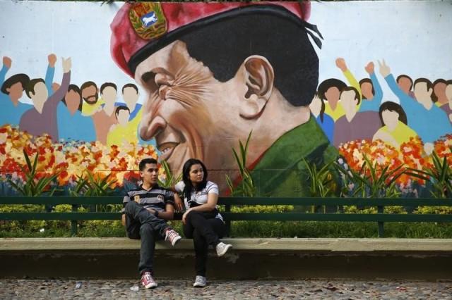 Una pareja se sienta frente a un mural del fallecido líder socialista de Venezuela, Hugo Chávez en Caracas